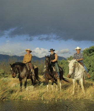 Three Cowboys on horses by a river with stormy skies